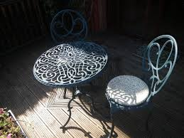 wrought metal small garden table and two matching chairs with cushion pads lovely set
