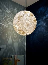 the doily lamp is a breath taking thin skin around a light reflecting designs on