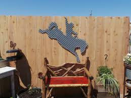 large corrugated metal bronc rider wall