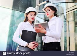 Two Young Pretty Business Women Industrial Engineers In Construction