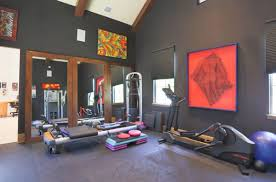 home gym furniture. large glass windows visually connect the home gym with canopy outside view in gallery bright artwork on walls adds color to dark room furniture