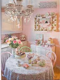 small shabby pink dining area with dishware wall display and crystal chandelier