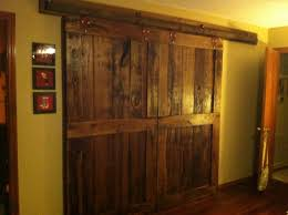 reclaimed wood sliding barn doors with big metal rod hanging on yellow bedroom wall plus three picture frame as decor