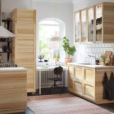 A White Kitchen With Traditional Natural Ash And Glass Cabinets.