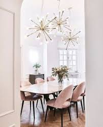 herringbone wood floors pink velvet chairs multiple light fixtures over dining table gorgeous dining room