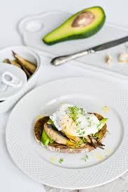 Black Bread Sandwich With Avocado Poached Egg And Sprats Photo
