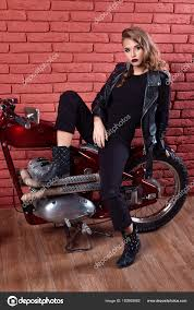 coveted woman or girl in a leather jacket and tight pants boots sits on a motorcycle with an unusual hairdo and make up on a brick red wall photo by