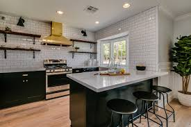 white kitchen cabinets with brass cup pulls and butcher block