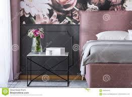 Bloemen Op Zwarte Lijst Naast Roze En Grijs Bed In Slaapkamer Inte