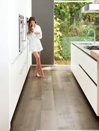 example of extra wide plank wood floor by porcelanosa with white kitchen also white slab