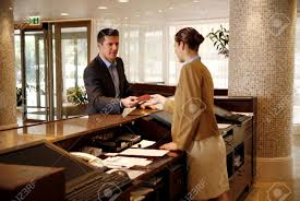 man checking in at hotel reception desk stock photo 24736314