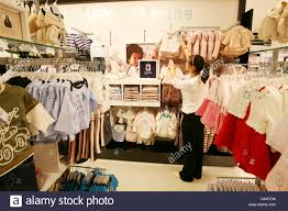 a shop assistant arranging children s clothes on a rail in a large a shop assistant arranging children s clothes on a rail in a large department store