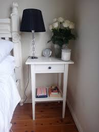 narrow wood bedside table lamp in the corner painted with white color with drawer and storage plus bedside lamp with crsytal stand and black lampshade ideas