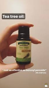 holding up tea tree oil bottle