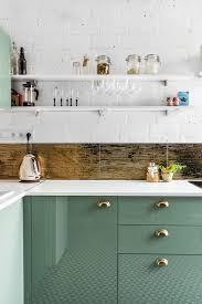 Salbeigrüne Küche und goldene Fliesen als Spritzschutz