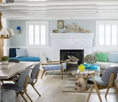 driftwood over the mantel and as the base of a table add to the modern coastal look of this open floor plan living space image house beautiful