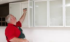 man attaching frosted doors to the cabinet