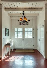 tanooga salvage southeastern salvage farmhouse entry and chandelier exposed beams framed artwork white ceiling white console