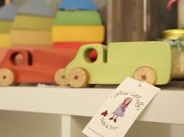 brightly coloured wooden toy trucks on a shelf