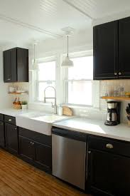 black kitchen cabinets, ikea farmhouse sink, white counters and subway tile  - https: