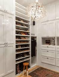 an elegant walk in closet boasts built in shoe shelves and boot shelf flanked by floor to ceiling cabinets to the left and open shelving and a small dress