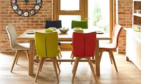 the gigi dining table and multi colored dining chairs covered in boiled wool
