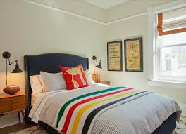 fantastic boy s room features tan walls adorned with a high chair rail framing a navy bed with silver nailhead trim on queen bed dressed in ticking stripe