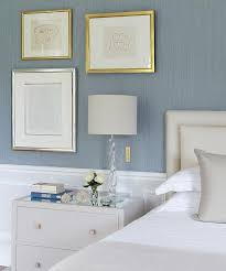 blue and grey bedroom features upper walls clad in blue grasscloth and lower walls clad in wainscoting lined with a cream headboard on bed dressed in white