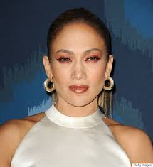 we applaud j lo for stepping out of the box and trying a bold new makeup look however this red orange eyeshadow and lip color seems plastered on her skin