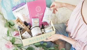 woman holding an open therabox subscription box full of self care skin and spa s