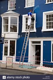 main using a ladder painting outside wall of house beaumaris wales uk stock image