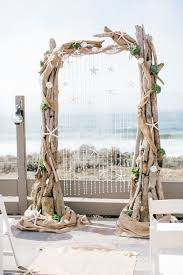 large driftwood wedding arch decorated with ss and star fish
