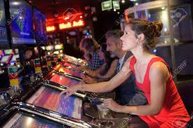Cheerful Pretty Woman Playing Slot Machines In Casino Stock Photo, Picture  And Royalty Free Image. Image 82182921.