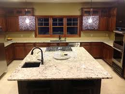 medium toned wood cabinets warm up this kitchen with delicatus granite kitchen counters and island