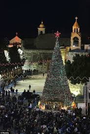 A 55-foot Christmas tree towers above the revelers outside the Church of  the Nativity