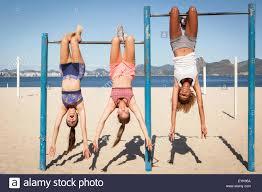 Drei Junge Frauen Die Kopfüber Hängend Bar Am Strand