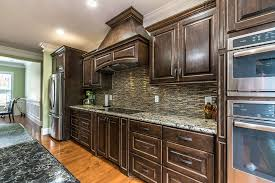 delicatus white granite kitchen countertops matched with earth toned tile backsplash and dark brown cabinets
