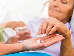 Homecare Nurse Helping Elderly Lady To Take Her Daily Medicine