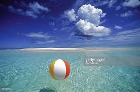 beach ball in ocean. French Polynesia, Bora Bora, Calm Ocean With Beach Ball Foreground Patch Of Sand Background Blue Sky Clouds In U
