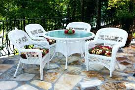 white wicker patio dining set with round glass top table and fabric chair cushions on balcony