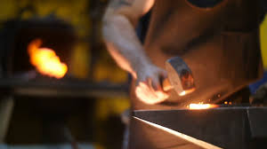 blacksmith workshop. blacksmith hammering hot metal on an anvil with sparks in a workshop behind him forge stock video footage - videoblocks