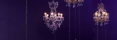 three vintage crystal chandeliers hanging at various heights in front of a deep violet hued backdrop new arrivals