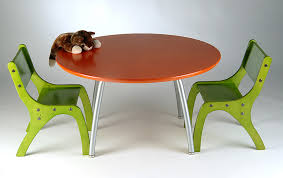 larger round table with lightweight metal legs a pair of green painted wood chairs an animal
