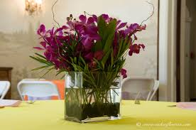 wedding centerpieces 034 purple orchid centerpiece with mixed greenery in a square glass vase accented with black river rocks