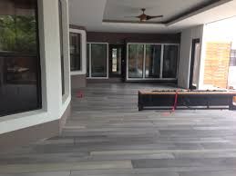 this plain ordinary bare concrete patio got a sleek and modern makeover with a stunning contemporary linear tile in a muted charcoal palette