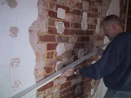 drywall over a rendered plaster wall