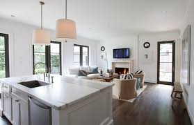 open floor plan kitchen features twin linen drum light pendants over calcutta marble kitchen island