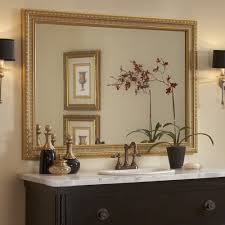 this traditional dark wood bathroom showcases the providence gold mirror frame atop the wall mounted
