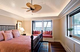 classic tray ceiling design uses an artistic fan to accentuate the beauty of this bedroom