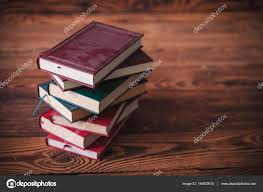 pile of dusty old books on a wooden background stock photo